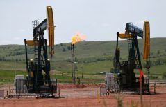 FILE -In this June 12, 2014 file photo, oil pumps and natural gas burn off in Watford City, N.D. The Interior Department says it is replacing an Obama-era regulation aimed at restricting harmful methane emissions from oil and gas production on federal lands. A rule being published in the Federal Register this week will replace the 2016 rule with requirements similar to those that were in force before the Obama administration changed the regulation. (AP Photo/Charles Rex Arbogast, File)